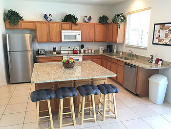 A fully equipped kitchen with granite countertops.