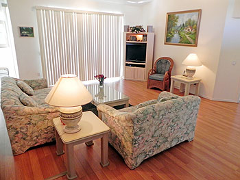 Homely living room with large LCD screen and comfortable 3 and 2 seaters.